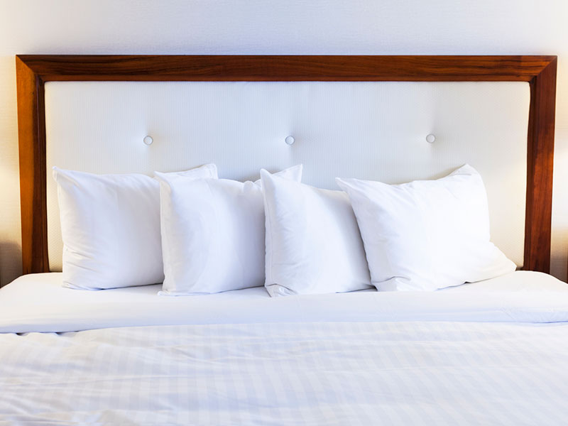 White bed and headboard, with four white bed pillows.